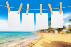 Blank white papers hanging on rope on beach. White blank hang rope papers background design stock photo