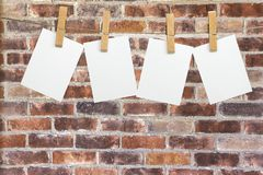Blank white papers hanging on rope on brick. White blank hang rope papers background design Royalty Free Stock Photo