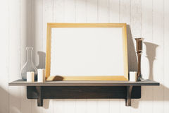 Blank white picture frame with candlesticks on brown wooden shel Stock Image