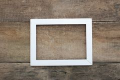 Empty White Picture Frame Old rustic Wooden wall floor. copy space. Blank white picture frame on the wall and the floor stock image