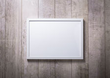 Blank white picture frame on the wood wall.  Royalty Free Stock Photo