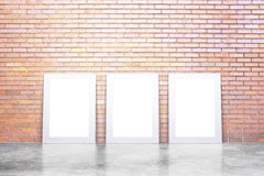 Blank white picture frames on concrete floor and red brick wall, Stock Photos
