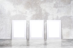 Blank white picture frames in empty loft room with concrete floo. R and wall, mock up Stock Images