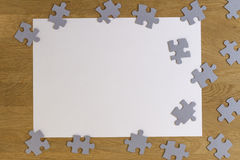Blank white piece of paper surrounded by puzzle pieces on wooden background. Top view. Copy space for text Royalty Free Stock Image