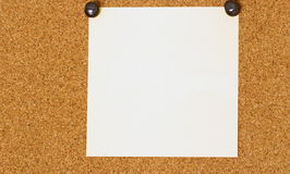 Blank white post-it on a coarkboard background Royalty Free Stock Photography