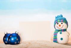 Blank white postcard, snowman , Christmas balls in  sand onseashore. Royalty Free Stock Image