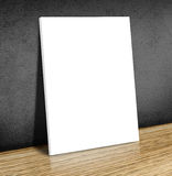 Blank white poster frame at wooden floor and black concrete wall Stock Photography