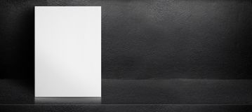 Blank white poster leaning at black interior cement room background,mock up banner template for display of design,leave side space royalty free stock images