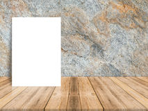 Blank white poster leaning at tropical wood table top with dark royalty free stock images