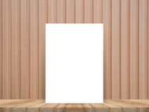 Blank white poster leaning at tropical wood table top with plank wood wall,Mock up background. Royalty Free Stock Photo