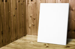 Blank white poster leaning at wooden wall in plank wood room,Mock up for adding your content. Blank white poster leaning at wooden wall in plank wood room,Mock royalty free stock images