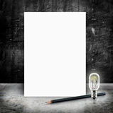 Blank White poster with lightbulb and pencil in a glossy concret Royalty Free Stock Photos