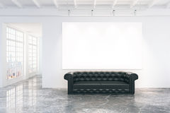 Blank white poster on white wall with black leather sofa on conc Stock Photo