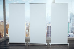 Blank white posters on black wooden floor and glassy walls with Stock Photos