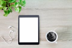 Blank white screen tablet computer with hot coffee cup, earphone and green plant pot on wooden desk. Business concept Stock Photos