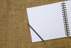Blank white sketch book and black pencil with space on hessian fabric background royalty free stock images