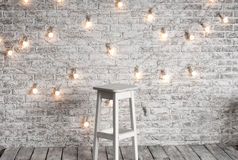 Blank white stool against the backdrop. Of a brick wall with a garland of light bulbs Royalty Free Stock Photo