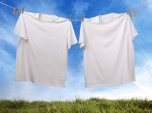Blank white t-shirt hanging on clothesline. White t-shirt hanging on outdoor clothesline with blank front ready for logo or message stock images