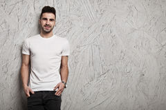Blank white t-shirt on man`s body. Smiling man in white blank t-shirt, and OSB wooden wall background Royalty Free Stock Images
