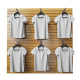 Blank white t-shirts hanging on wooden shop stand, isolated on white background Stock Photography