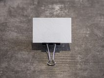 Blank business card held by a binder clip on a wooden surface stock photography