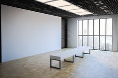 Blank white wall in exhibition hall. Side view on loft style empty exhibition white blank banner in gallery with white bench on parquet floor and floor-to Royalty Free Stock Images