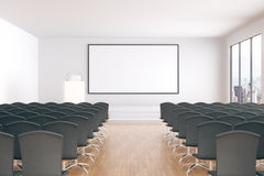 Blank whiteboard in conference room. Blank whiteboard in conference hall interior with rows of seats, wooden floor, concrete walls and window with city view Stock Photos