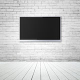 Blank wide screen TV. On brick wall in room Stock Image