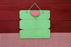 Blank wood menu sign by red gingham tablecloth hanging on wooden background. Blank antique green sign with red checkered heart and red checkered napkin on red Royalty Free Stock Photos