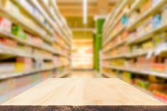Blank wood table top or shelf with blurred shop shelves background. Suitable montage or display your products stock photography