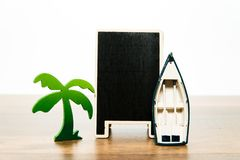 Blank wooden black board with green palm tree and white boat Stock Images