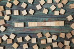 Blank wooden block leaning on a structure made of many other blocks with several of them still lying scattered on a textured. Rustic wooden desk. Conceptual of stock photography