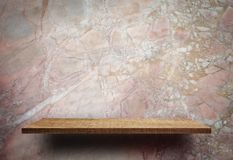 Blank wooden display shelf on marble wall stock images