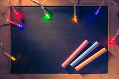 Blank wooden framed chalkboard with color chalks and holiday lig Royalty Free Stock Photos