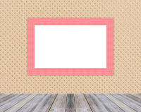 Blank wooden photo frame leaning at cloth wall and diagonal wood floor. Stock Photos