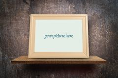 Wooden photo frame mock up on grungy wall stock photo