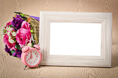 Blank wooden photo frame and pink alarm clock. Royalty Free Stock Images