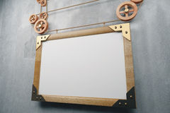 Blank wooden picture frame in steampunk style on concrete wall, Stock Image