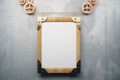 Blank wooden picture frame steampunk style on grey concrete wall Stock Image