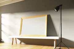 Blank wooden picture frame in a sunny gallery with benches and l Stock Photo