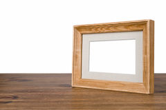 Blank wooden picture frame on table over white background Stock Images