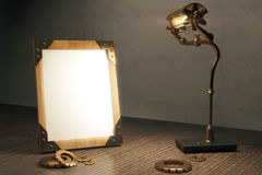 Blank wooden picture frame with vintage lamp on wooden table in Royalty Free Stock Photos