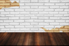 Blank wooden shelf with leaf frame on peeling paint on brick wal Stock Image