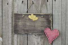 Blank wooden sign hanging on wood door with gingham and gold hearts Stock Image
