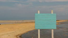 Blank Wooden Sign Painted Pastel Blue/ Teal Color on Empty Sandy stock photo