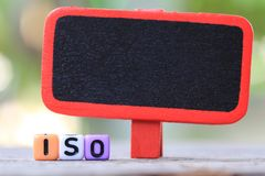 Blank wooden sign and plastic text box of ISO. Stock Photography