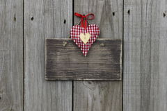 Blank wooden sign with red gingham and gold hearts hanging on wood background. Blank wooden sign with red gingham and gold hearts with red ribbon on wooden Stock Photo