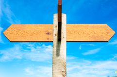 Blank wooden signpost with two arrows over clear blue sky with copy space Royalty Free Stock Image