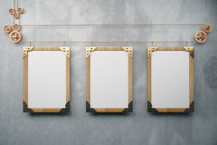 Blank wooden steampunk picture frames on grey concrete wall, moc Stock Photos