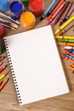 Blank writing book, open white page, art equipment, copy space, vertical on school desk Stock Photography